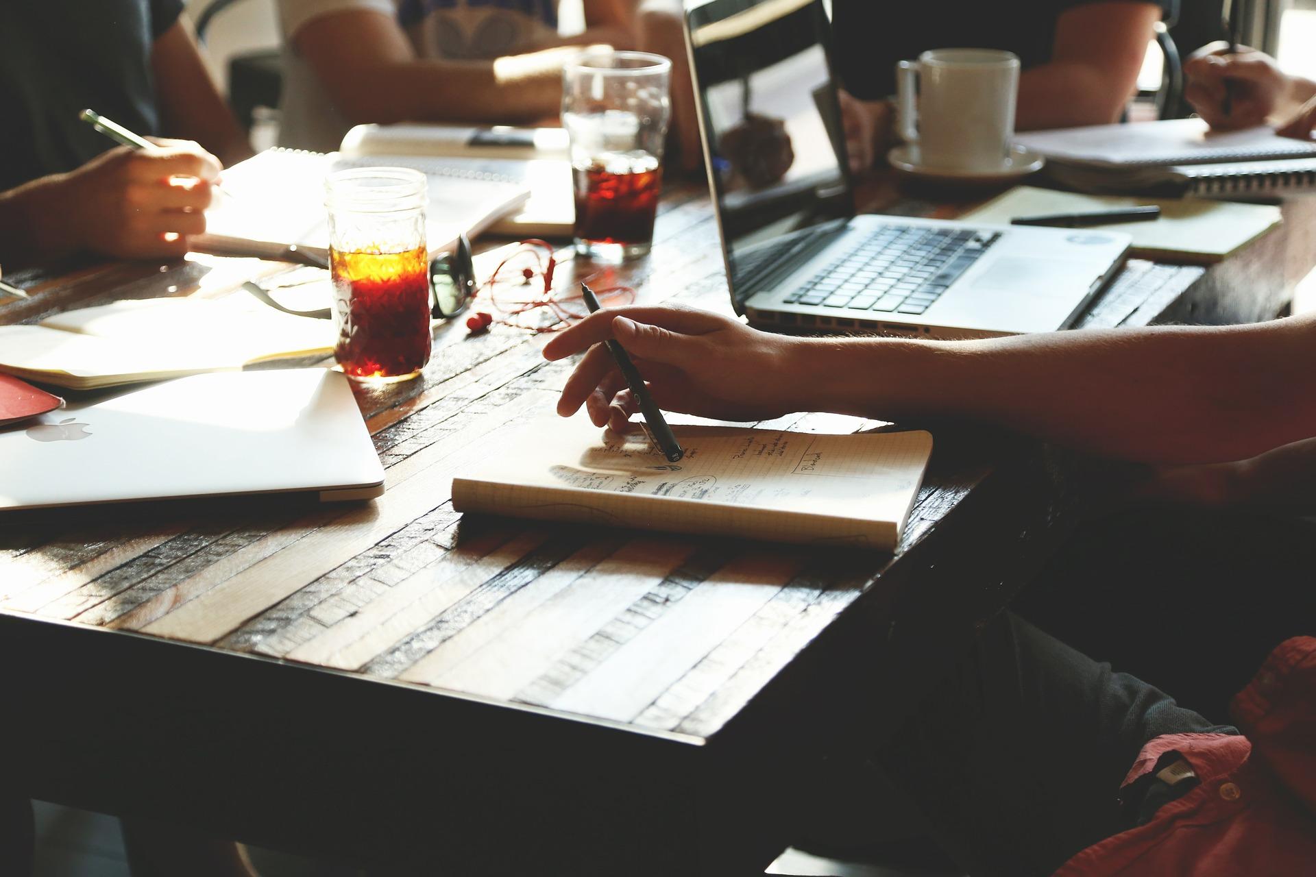 Personen sitzen um einem Tisch und sind am Arbeiten.