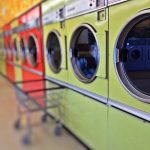 Waschmaschinen in einer Reihe un ein kleiner Korb auf Rollen.