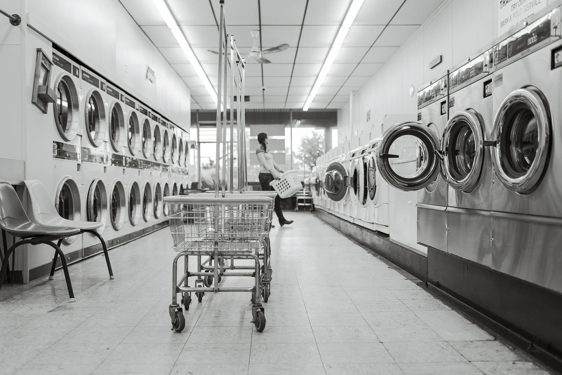 Waschmaschinen in einem Waschsalon, eine Frau hält einen Waschkorb.