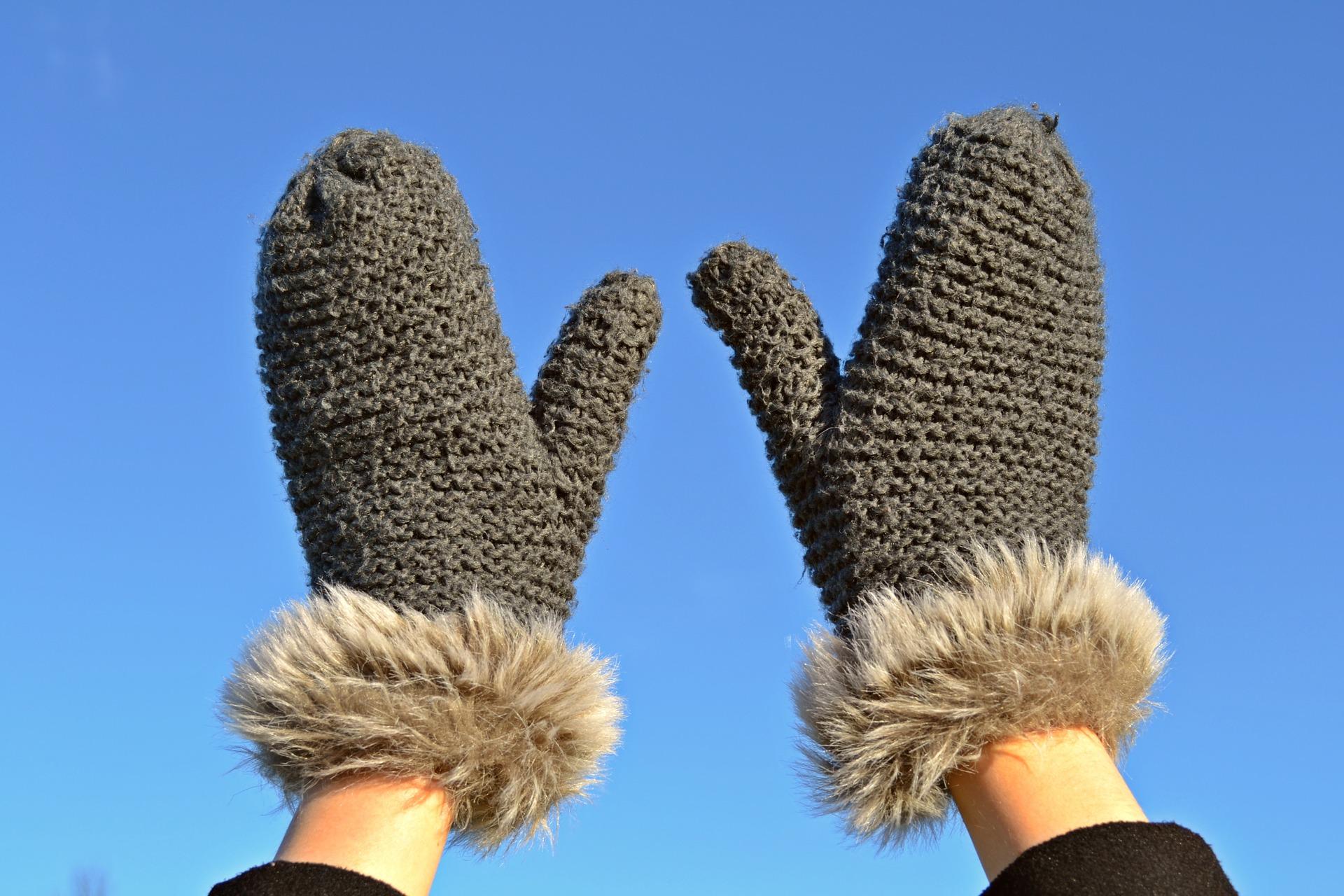 Eine Person hält die Hände in die Luft und trägt Handschuhe.