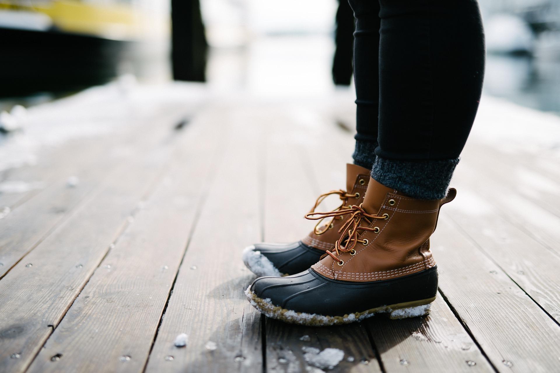 Beine einer Person, trägt Winterstiefel und dicke Socken.