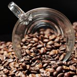 Eine Tasse aus Glas in einem Haufen von Kaffeebohnen.