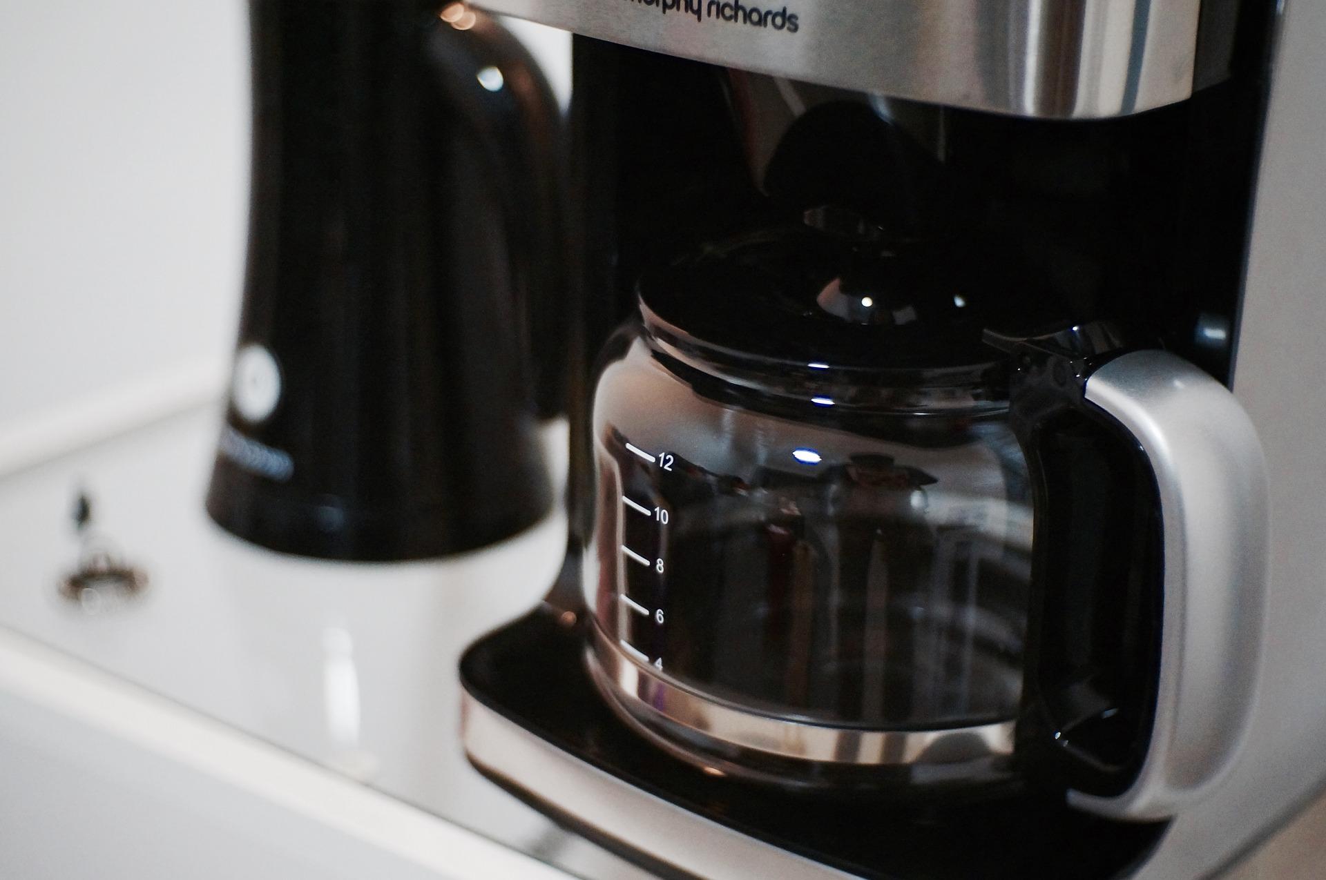 Filterkaffeemaschine, daneben steht eine schwarze Kaffeekanne